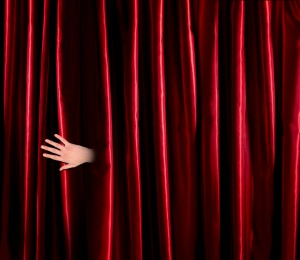 hand emerging from behind red theatre curtain
